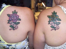 Twin sister flower tattoos on girls' shoulder back.