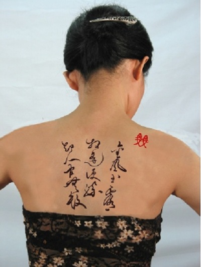 The Japanese script calligraphy tattoo at girl's upper back.