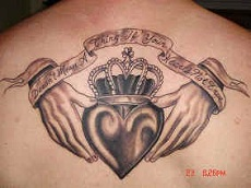 A claddagh tattoo at man's upper back.