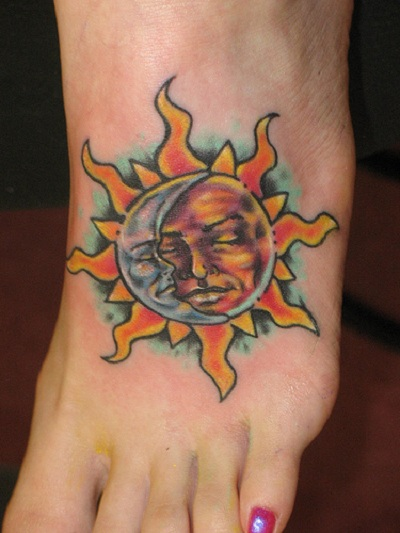 A moon sun tattoo on female's left foot.