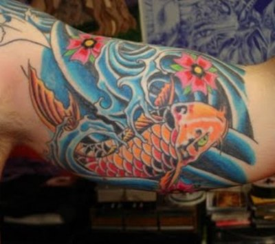 The orange and yellow color koi fish tattoo on man's arm.