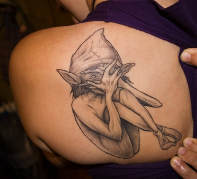 A closing face elf tattoo design on woman's left shoulder blade.