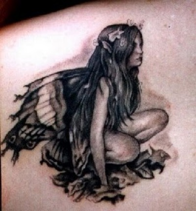 A dark color fairy tattoo on shoulder blade.