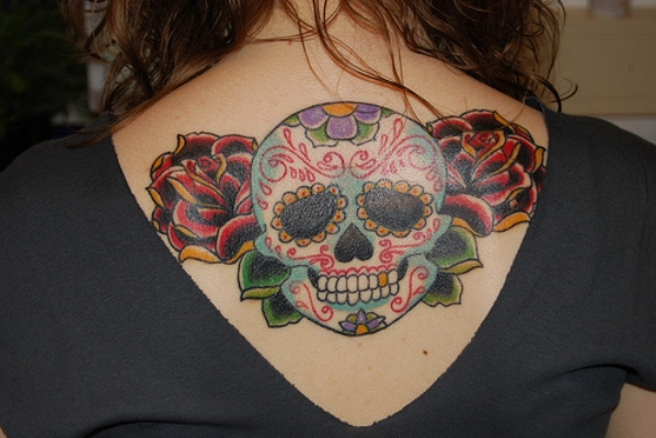 Teo roses with girly skull tattoo at girl's upper back.