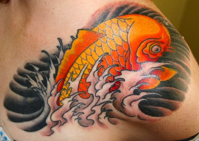 A koi fish tattoo on man's left shoulder.