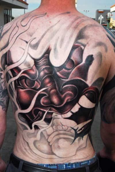A huge Japanese mask tattoo at Japanese guy's back.