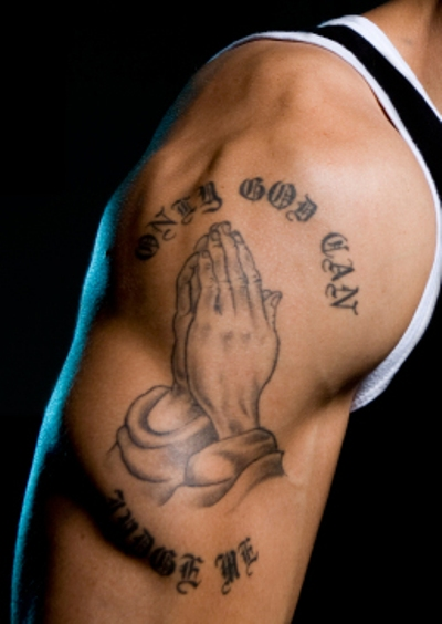 "A simple praying hands with ""ONLY GOD CAN JUDGE ME"" tattoo on man's right arm."