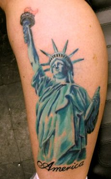 "A statue liberty with ""America"" tattoo design on calf."