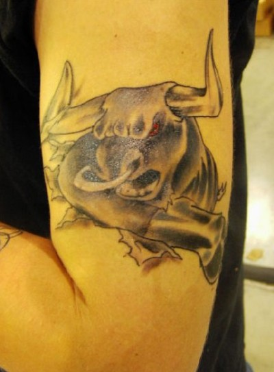 A red eyes Taurus tattoo on man's left arm.
